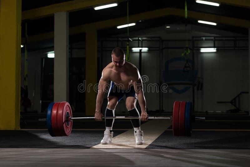 Atleta novo que prepara-se para o treinamento do levantamento de peso imagens de stock