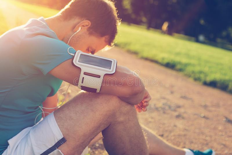 Atleta novo que senta-se e que descansa após o exercício no parque fotos de stock royalty free
