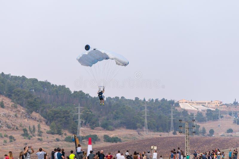 Atleta - o paramilitar desce com um paraquedas no campo no festival do balão de ar quente foto de stock royalty free