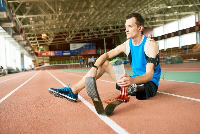 Atleta perjudicado Resting en pista corriente foto de archivo libre de regalías