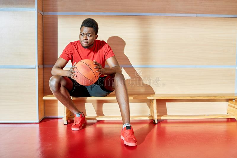 Atleta preto com a bola do basquetebol no banco foto de stock royalty free
