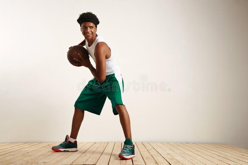 Atleta preto de sorriso dos jovens que joga o basquetebol imagem de stock royalty free