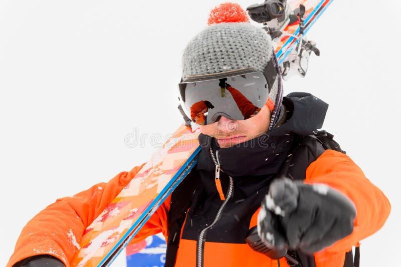Atleta profissional do esquiador em um terno preto alaranjado com uma máscara de esqui preta com os esquis em seus pontos do ombr fotografia de stock