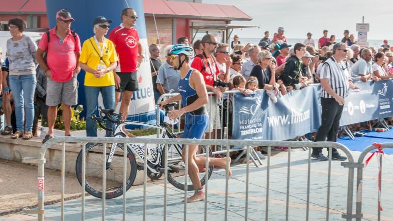 Atleta que corre com sua bicicleta ao curso da bicicleta imagens de stock royalty free