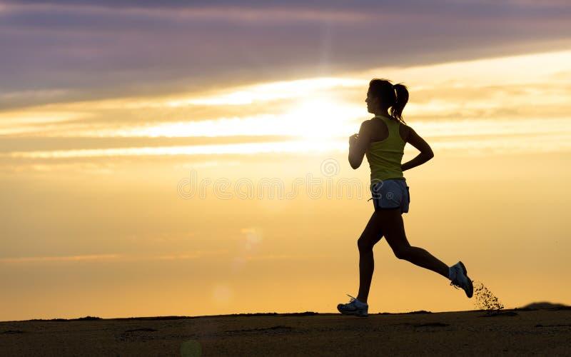 Atleta que corre no por do sol na praia foto de stock