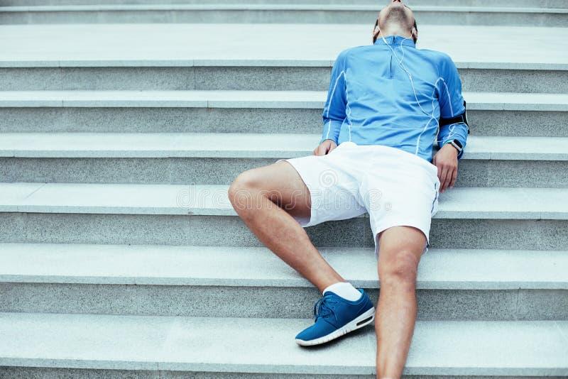 Atleta que encontra-se nas escadas após o exercício, na fita com telefone celular e nos fones de ouvido com música para treinar fotografia de stock royalty free