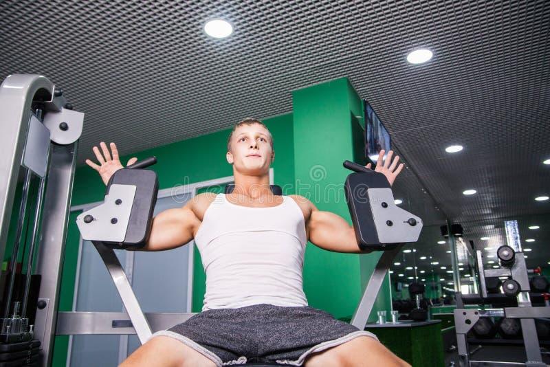Atleta que hace ejercicio del pecho en la máquina en gimnasio imágenes de archivo libres de regalías