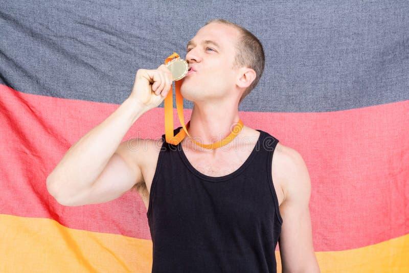 Atleta que levanta com a medalha de ouro na frente da bandeira alemão fotos de stock