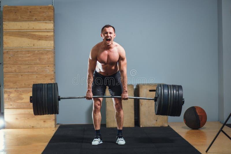 Atleta que lleva los pantalones cortos negros que levantan el barbell grande imagen de archivo