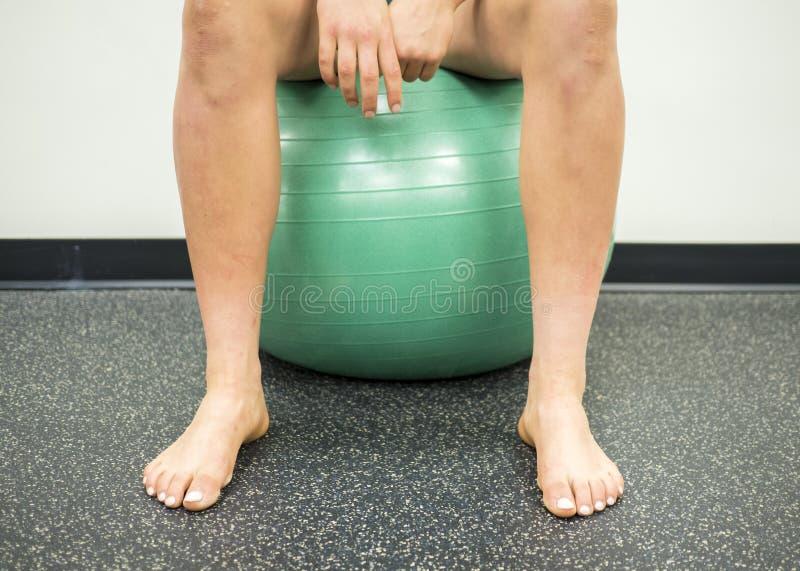 Atleta que se sienta en una bola verde del ejercicio que toma una rotura entre sus ejercicios foto de archivo