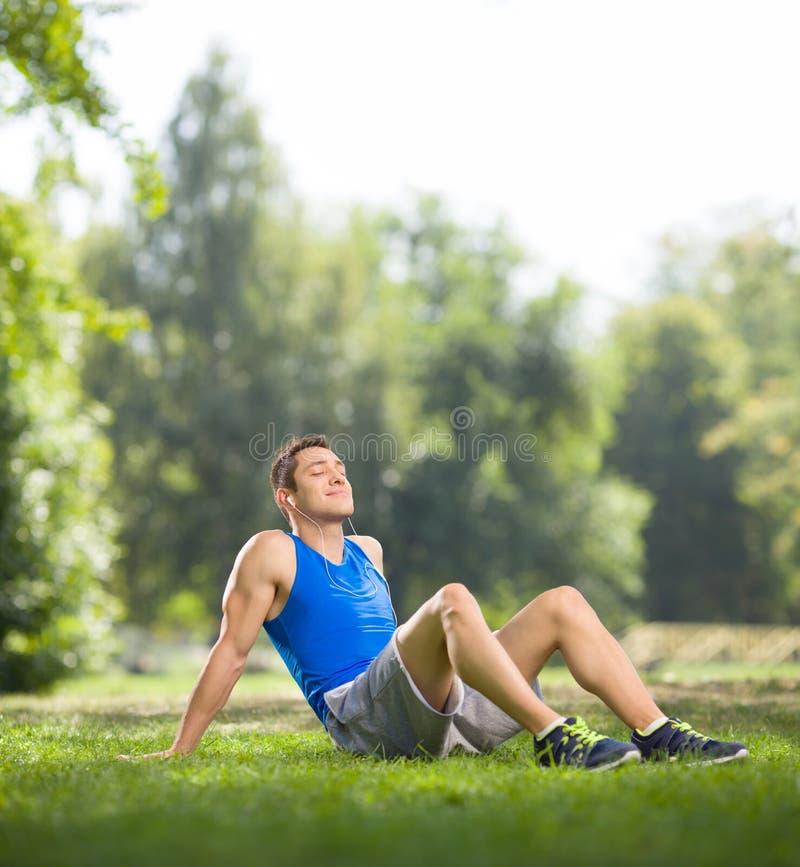 Atleta que senta-se no parque e na música de escuta imagens de stock royalty free