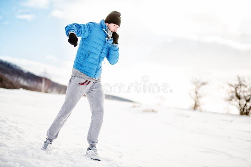 Atleta que tem um exercício para fora na neve, conceito da aptidão foto de stock royalty free