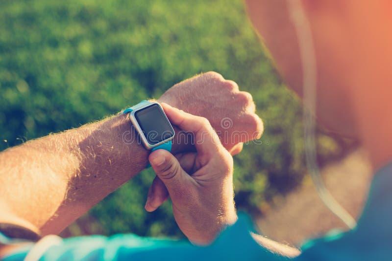Atleta que verifica seu relógio esperto no pulso imagem de stock