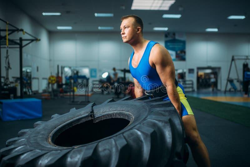 Atleta robi ćwiczeniu z ciężarową oponą, crossfit obrazy royalty free