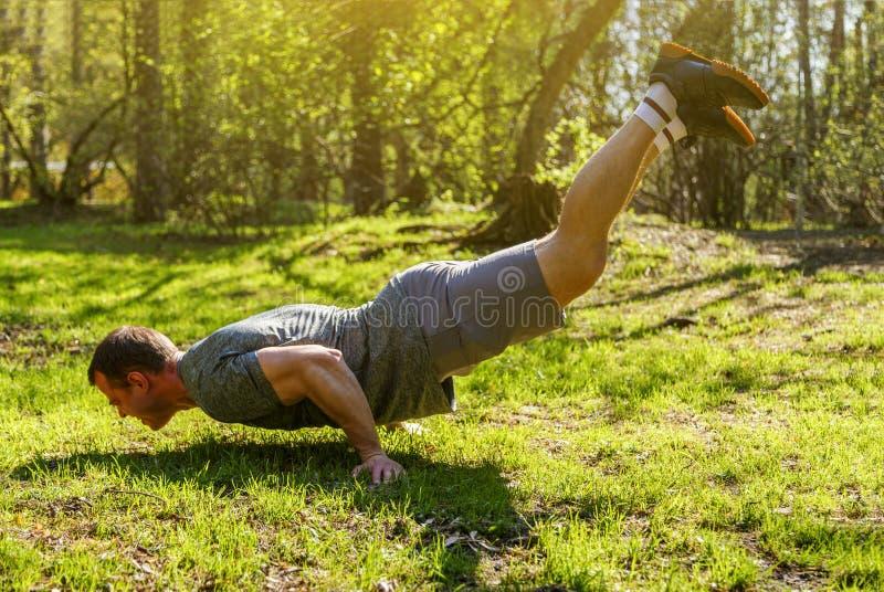 Atleta robi handstand z nogami podnosić obrazy stock