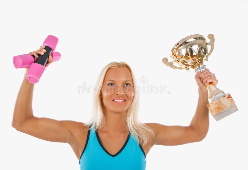 Atleta rubio sonriente con la taza de campeón imagen de archivo libre de regalías