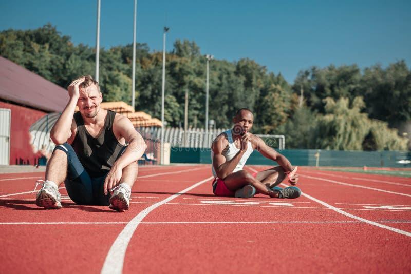 Atleta siedzi i cierpi przy stadium obraz royalty free
