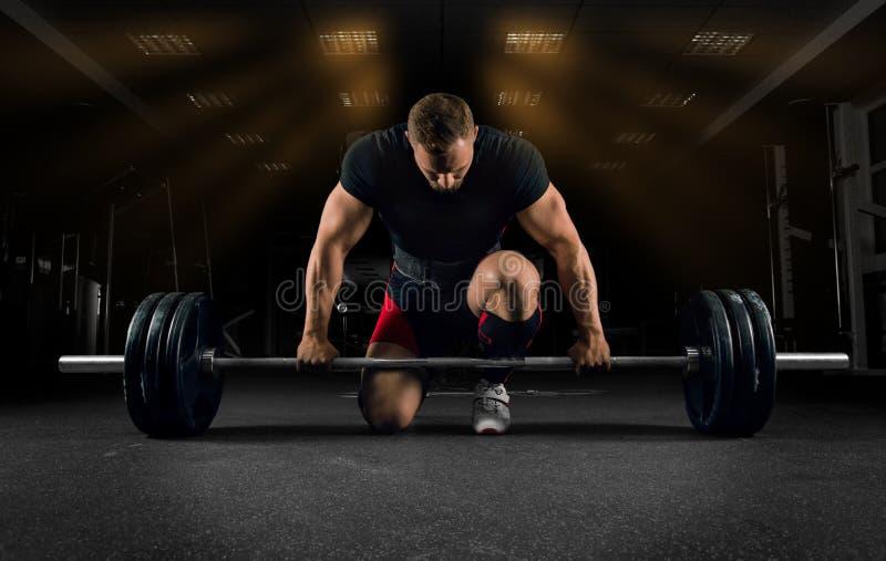Atleta stoi, jest preparin i na jego kolanie i blisko baru zdjęcie stock