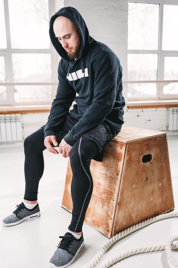 Atleta sudoroso que se relaja después de entrenamiento cruzado intenso en el gimnasio imágenes de archivo libres de regalías