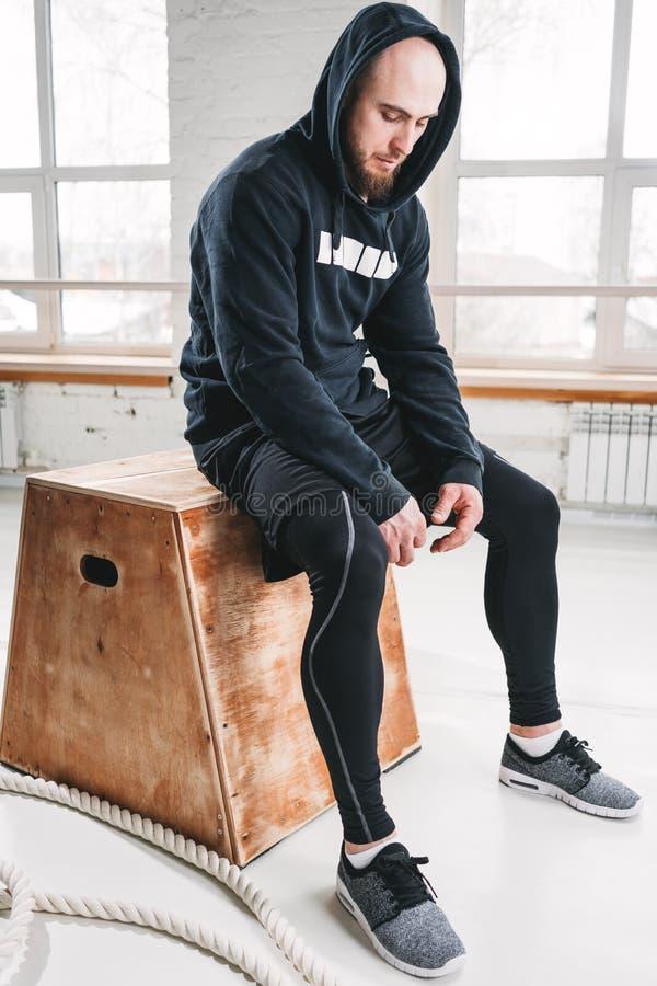 Atleta sudoroso que se relaja después de entrenamiento intenso del crossfit en el gimnasio imagenes de archivo
