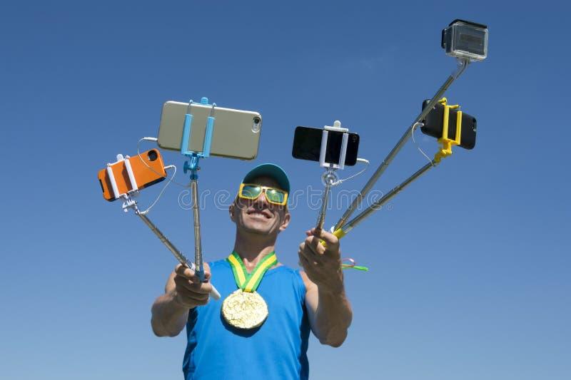 Atleta Taking Selfies da medalha de ouro com varas de Selfie foto de stock