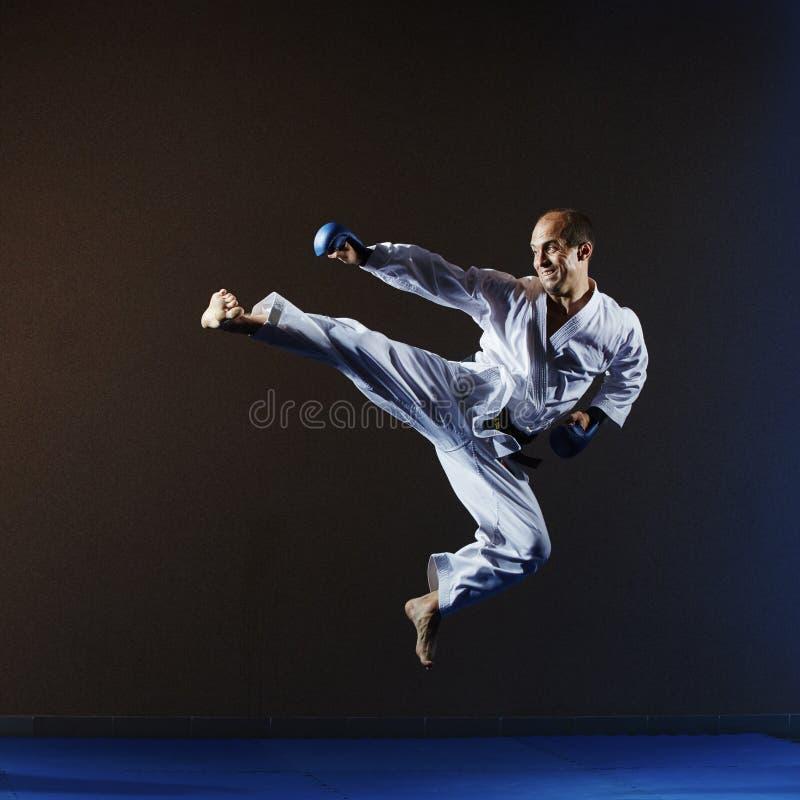 Atleta trenuje kopnięcie w skoku z błękitnymi narzutami na rękach zdjęcie stock