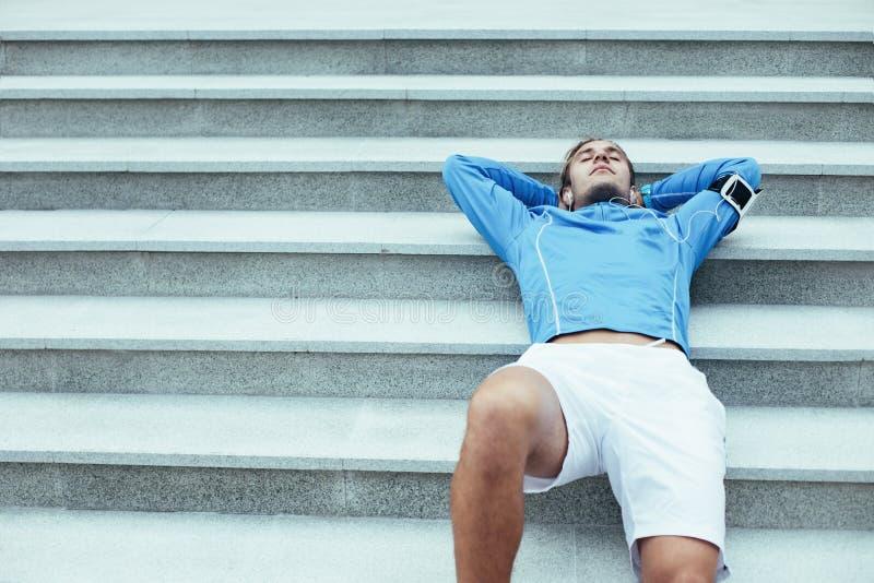 Atleta turbato che si trova sulle scale dopo l'allenamento, sul bracciale con il telefono e sulle cuffie con musica per preparars fotografia stock libera da diritti