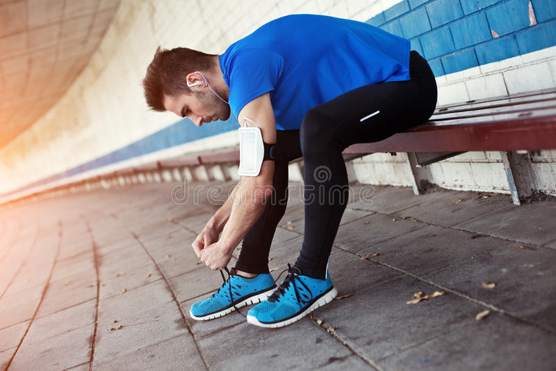 Atleta Tying Shoelaces foto de stock royalty free