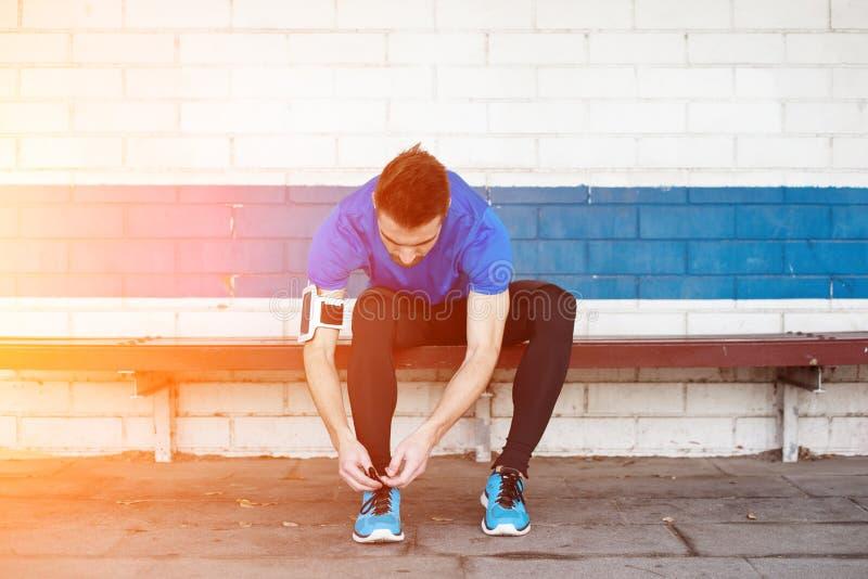 Atleta Tying Shoelaces foto de stock