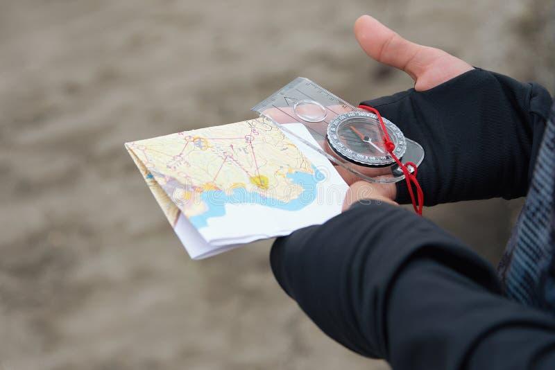 Atleta używa nawigaci wyposażenie dla orienteering, kompasu i topograficznej mapy, fotografia stock