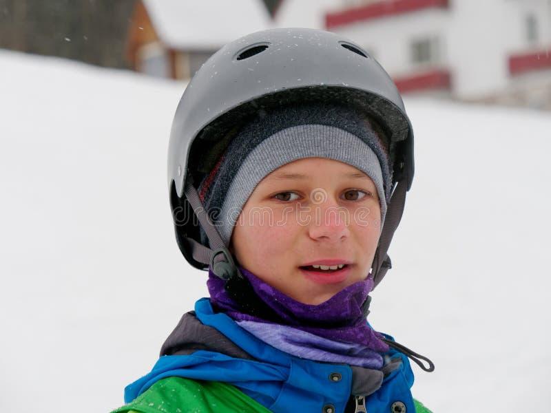 Atleta um esquiador em um retrato alegre do capacete na inclinação do esqui foto de stock