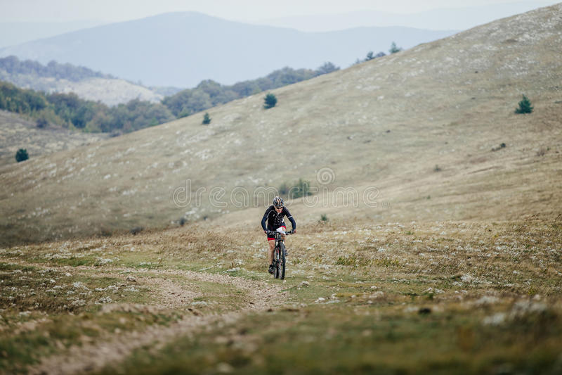 Atleta un montar a caballo del ciclista en mountainbike en un valle de la montaña imagen de archivo