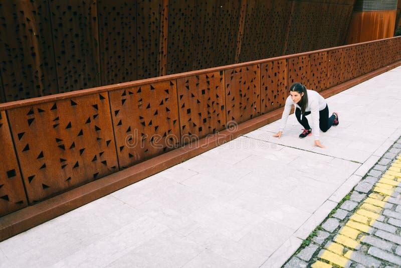 Atleta urbano de sexo femenino listo para correr foto de archivo