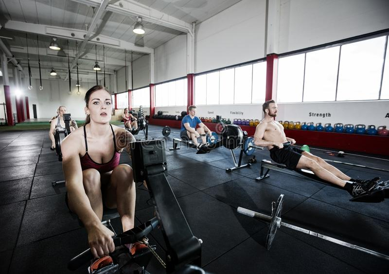 Atleta Using Rowing Machine con gli amici nel centro di forma fisica fotografia stock
