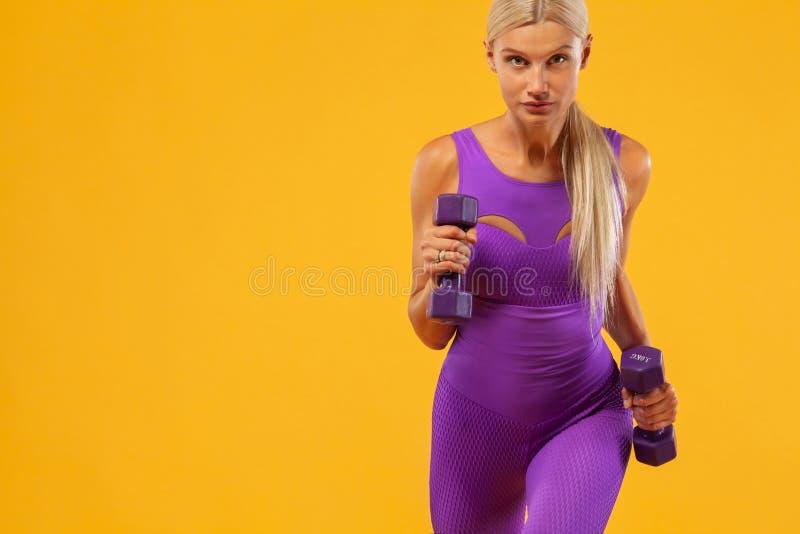 Atleta y culturista de la mujer de la aptitud que llevan a cabo pesa de gimnasia Aislado en fondo amarillo imágenes de archivo libres de regalías