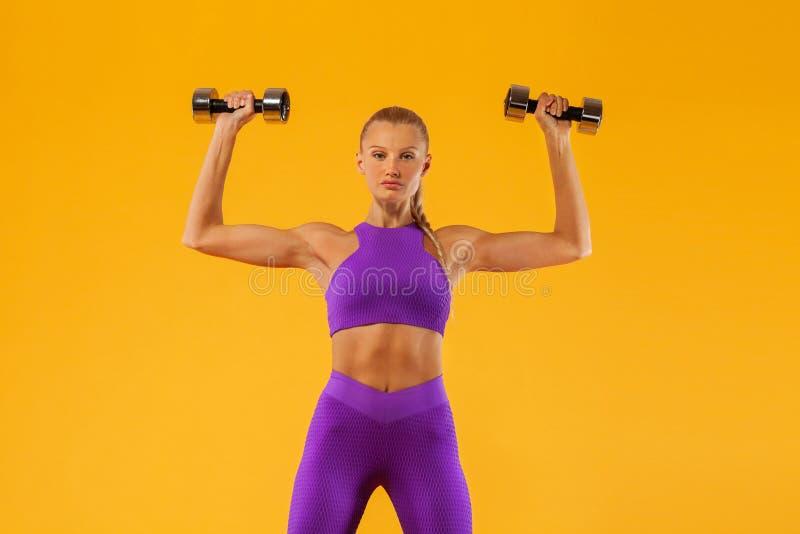 Atleta y culturista de la mujer de la aptitud que llevan a cabo pesa de gimnasia Aislado en fondo amarillo foto de archivo libre de regalías