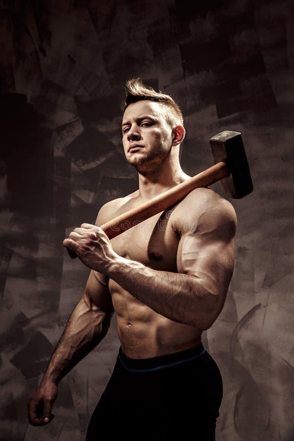 Atleta y martillo individuo con una aptitud agradable del músculo, martillo grande del metal del control del coche del culturista imagenes de archivo