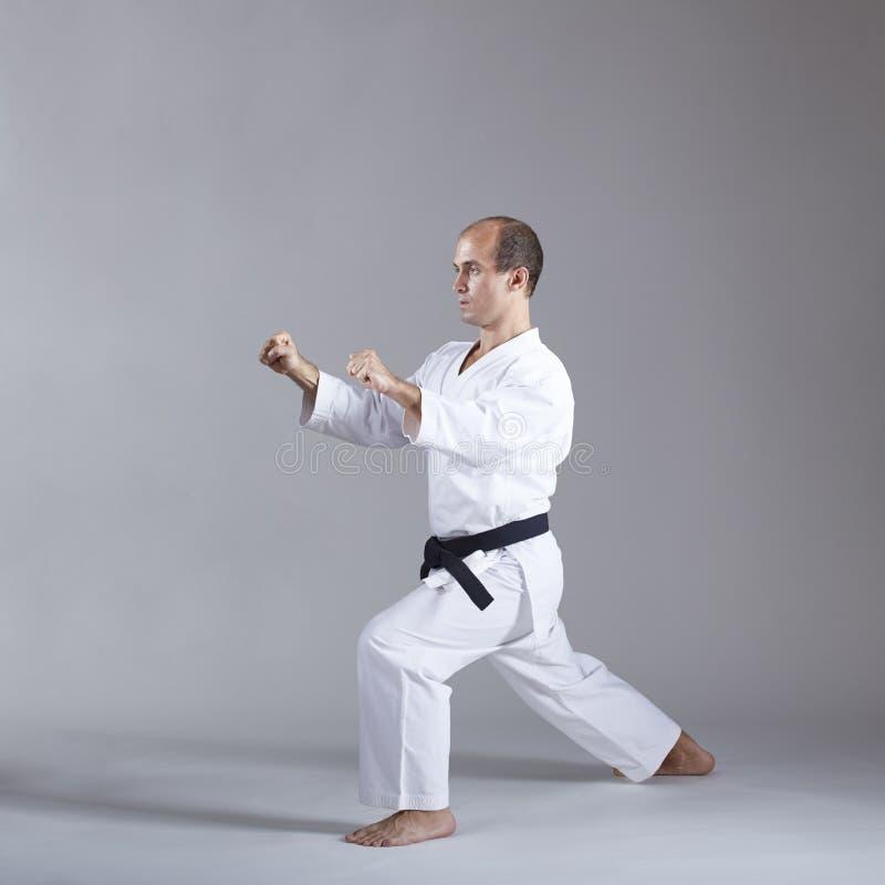 Atleta z czarnym paskiem w karategi i wykonuje formalnego karate ćwiczenie zdjęcia royalty free
