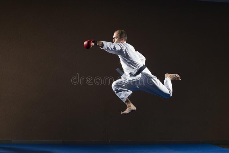 Atleta z czerwonymi narzutami na jego rękach trenuje poncz z jego ręką w skoku obraz stock