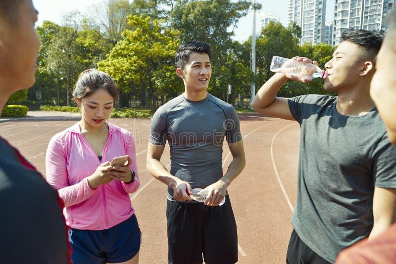 Atletas asiáticos jovenes que se relajan después de entrenar fotografía de archivo libre de regalías