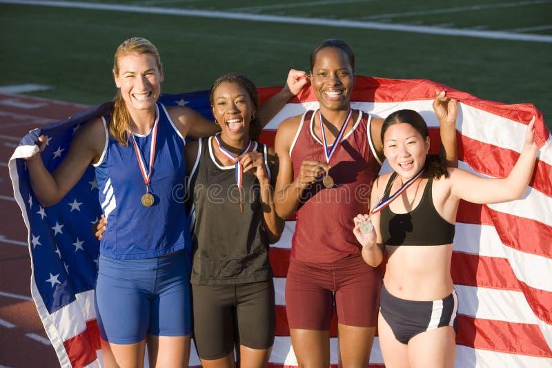 Atletas con la bandera americana y las medallas imagen de archivo libre de regalías