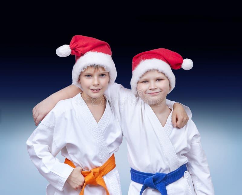 Atletas das crianças nos tampões de Santa Claus em um fundo do inclinação fotos de stock royalty free