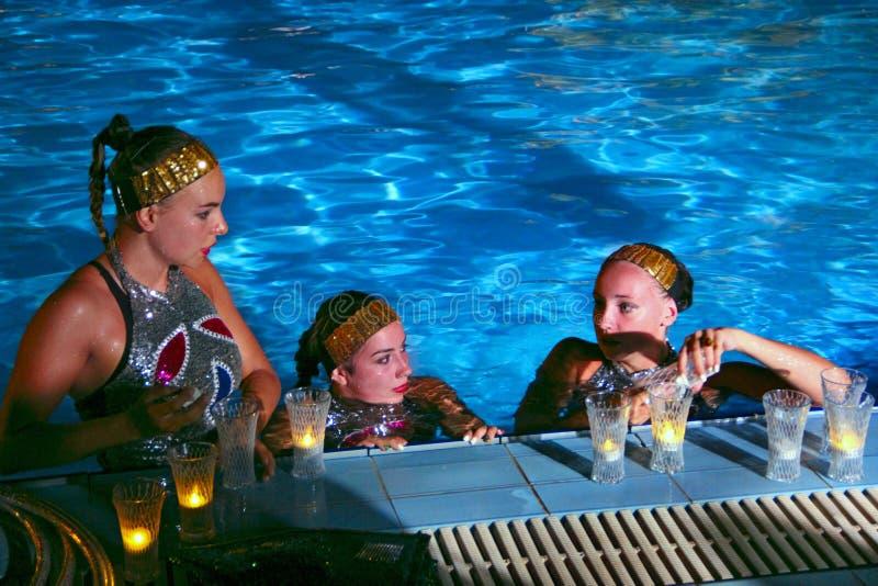 Atletas de las muchachas en la natación sincronizada preparar la demostración festiva con las luces en piscina imagen de archivo libre de regalías