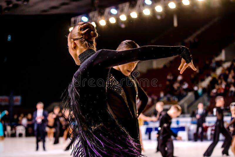 Atletas de los pares de la danza de los jóvenes que bailan el paso doble imagen de archivo
