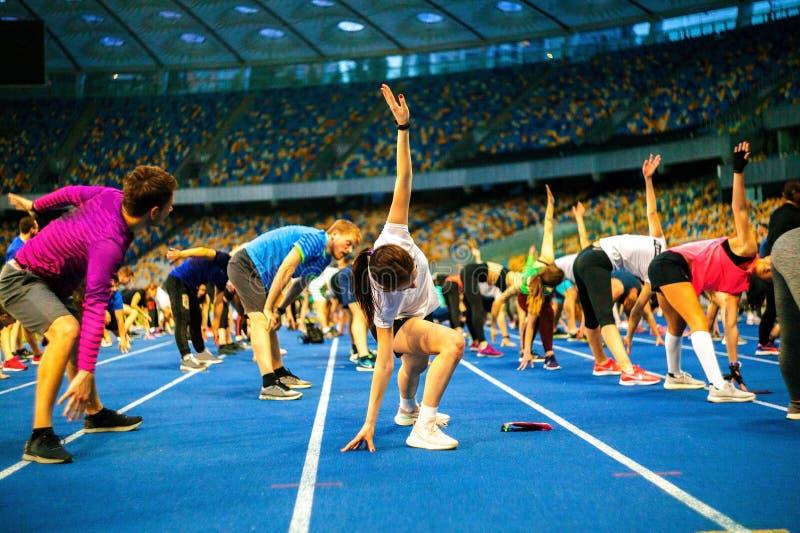 Atletas do grupo que treinam para a melhor flexibilidade da limitação no estádio fotos de stock royalty free