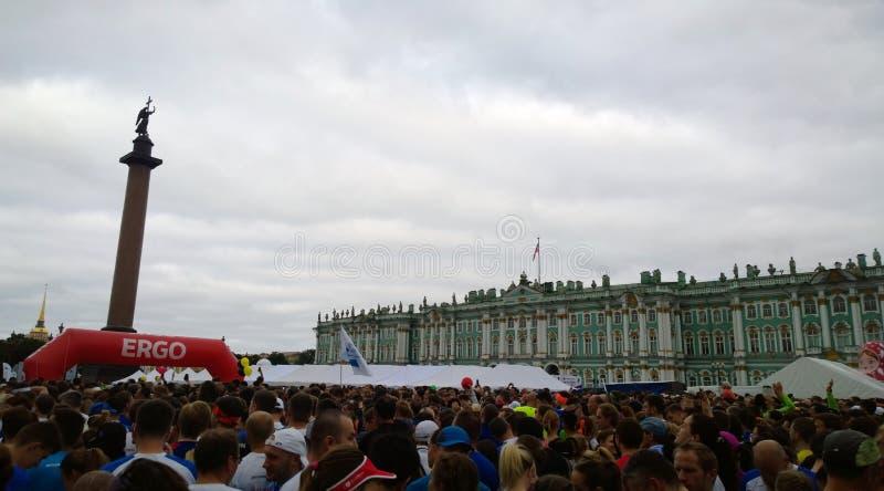 Atletas e fãs em grandes números que esperam o começo do ` das noites brancas do ` da maratona em St Petersburg no quadrado do pa fotos de stock royalty free
