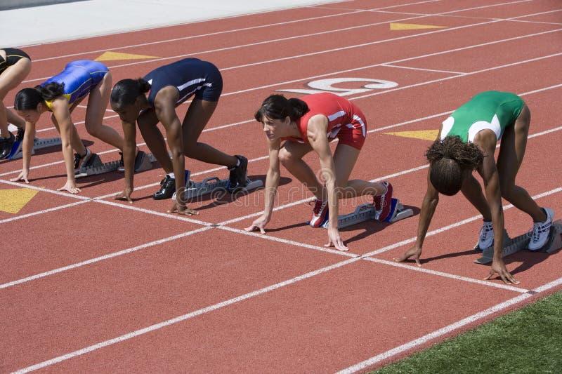 Atletas en el comienzo de la pista corriente imágenes de archivo libres de regalías