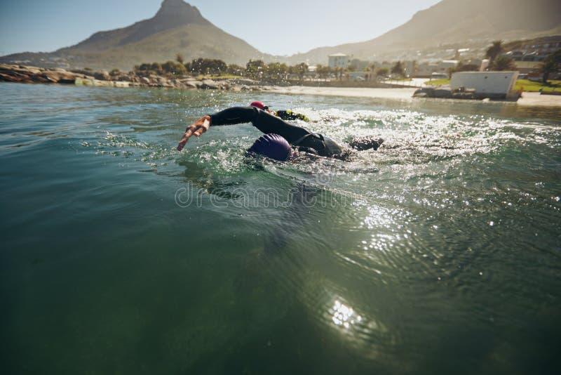 Atletas en el evento de la nadada de una competencia del triathlon imagenes de archivo