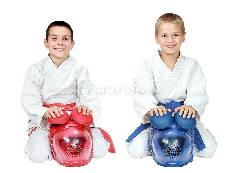 Atletas en el kimono que se sienta en un karate ritual de la actitud con los cascos aislados imagen de archivo libre de regalías