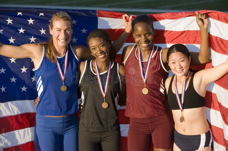 Atletas fêmeas entusiasmado multi-étnicos com bandeira americana e medalhas foto de stock royalty free